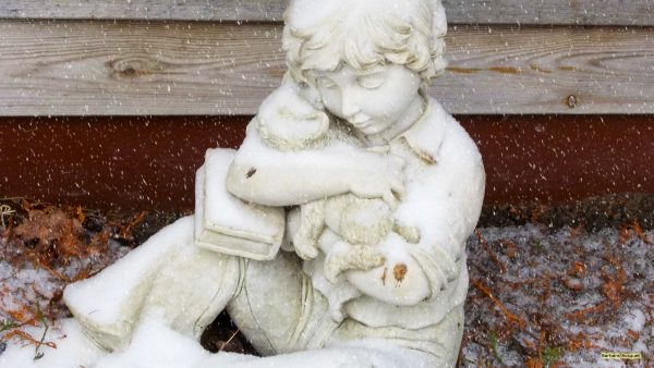 Statue child with dog and snow