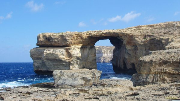 The Azure Window under a blue sky and a dark blue ocean.