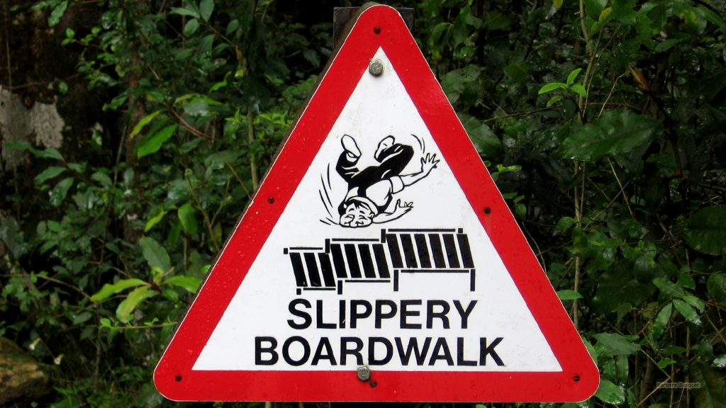 "Warning sign with a man falling, and the text""Slippery boardwalk""."