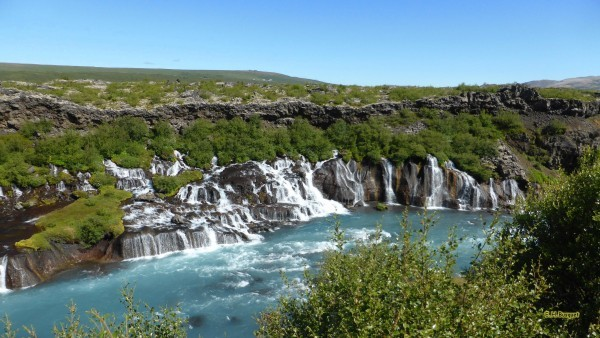 Hraunfossar falls under blue sky